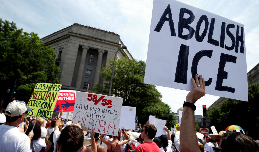 An immigration activist holds up a sign calling for the abolishment of ICE, U.S. Immigration and Customs Enforcement, during rally to protest the Trump Administration's immigration policy outside the Department of Justice in Washington, U.S., June 30, 2018.      REUTERS/Joshua Roberts - RC115555BB50