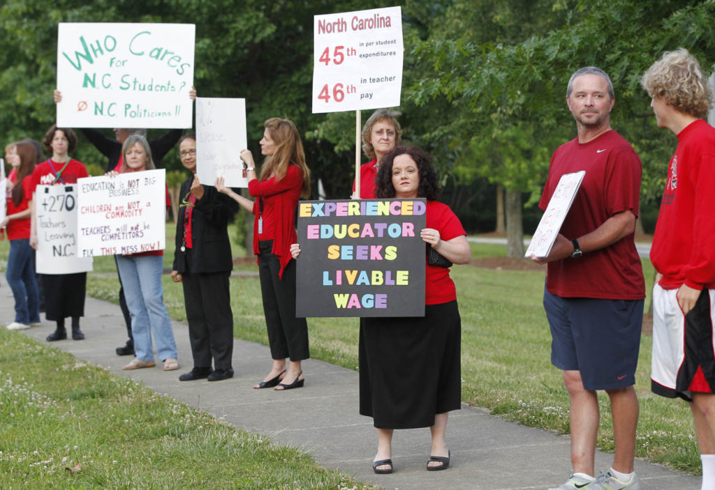 Teachers, including Kristin VanBuskirk, center, a math teacher at Apex High School, rally against high turnover and low pay on the sidewalk in front of Apex High School Wednesday morning, May 21, 2014.